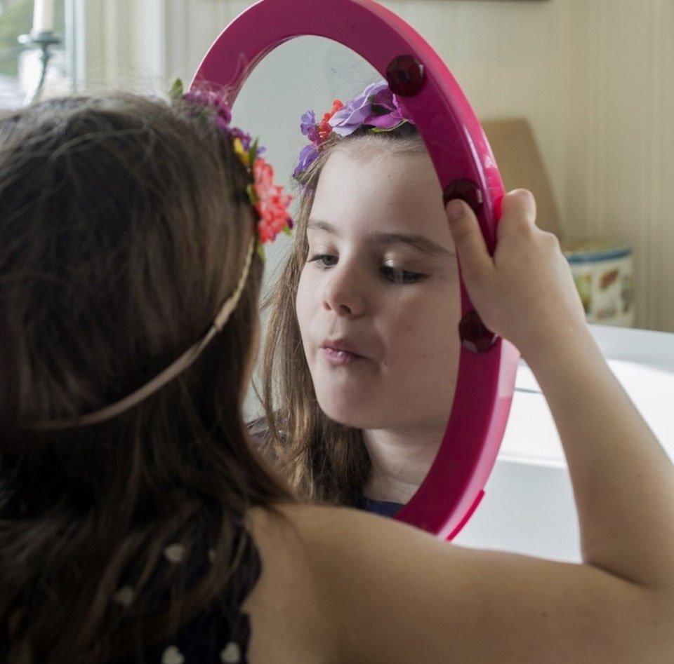 Ребенок смотрит в зеркало. Фотография для статьи Зеркало для детской комнаты
